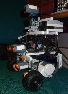 A Raspberry Pi Board with attached Brick Pi Board built into a robot  made of LEGO techinic elements. with two front wheels and a caster rear wheel.